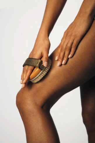 Woman exfoliating her leg with body brush