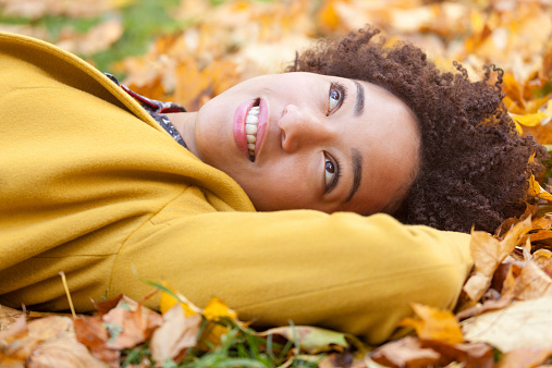 Woman with natural hair in autumn leaves