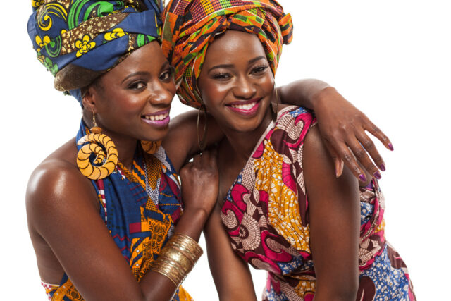 African women models posing in colorful dresses.